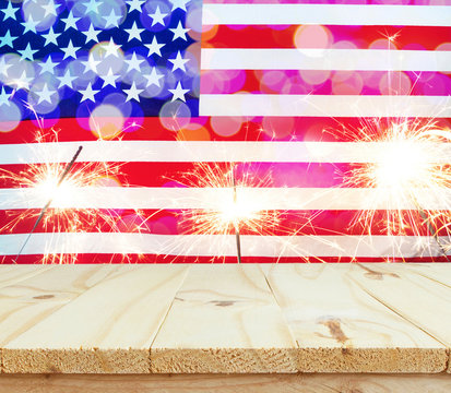 wooden table on USA flag with sparklers background celebrate American Independence Day of 4th July