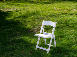 White Chair sitting on some vibrant green grass.