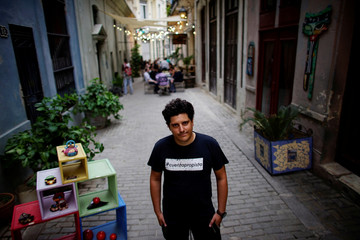 Self-employed Camilo Condis poses for a photo next to the restaurant where he works in Havana
