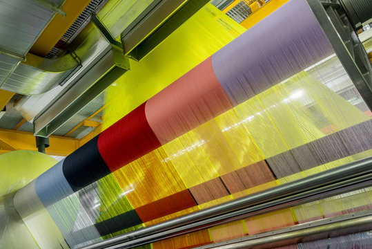 weaving loom at a textile factory, closeup. industrial fabric production line