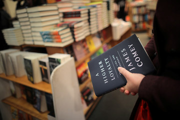 """A woman holds a copy of former FBI director James Comey's book """"A Higher Loyalty"""" at Kramerbooks book store in Washington D.C."""