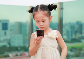 Little child girl in cream dress hold and looking photo in her hands at the rooftop of building.
