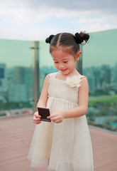Portrait little Asian child girl in cream dress looking photo in her hands at the rooftop of building.