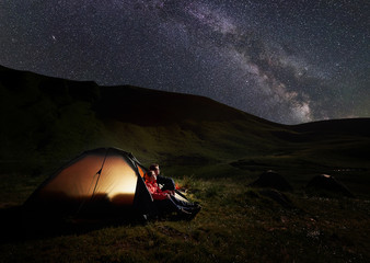 Man and woman having a rest at night camping in the Carpathians mountains near Dogyaska lake, sitting in tent, looking at the sky strewn with stars. In the tent lights on. Concept of active recreation