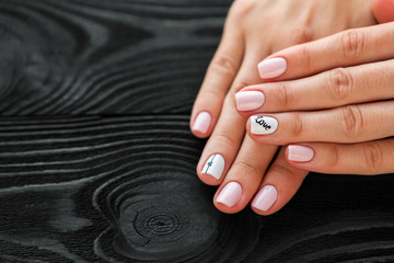 the manicure, pink with white color, isolated on a black wooden background