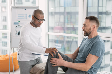 I feel pain. Good looking bearded man holding his leg while visiting a physical therapist