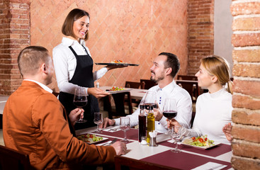 Female waiter carrying order for visitors