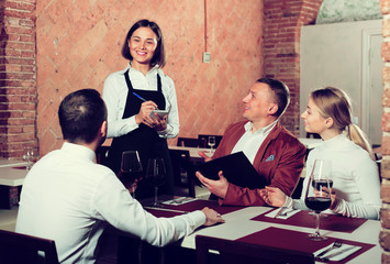 polite woman waiter receiving order from guests in restaurant
