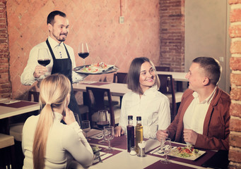Young waiter placing order in front of guests