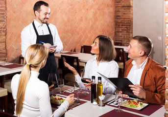 Man waiter receiving order from guests