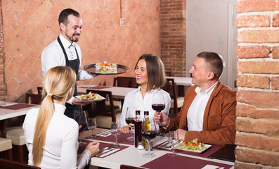 Smiling male waiter carrying order for visitors