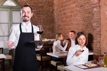 positive man waiter demonstrating country restaurant