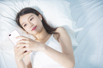 Woman use of mobile phone on bed