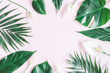 Summer tropical composition. Green tropical leaves and white flowers on pink background. Summer...