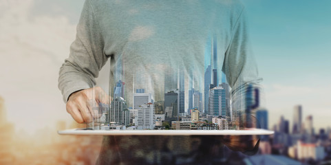 a man using digital tablet, and modern buildings hologram. Real estate business and building technology concept Wall mural