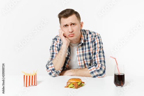 67636c4f Handsome sad upset young man sitting at table with burger, french fries,  cola in glass isolated on white background. Proper nutrition or American  classic ...