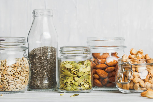 Various nuts and seeds in glass jars over white wooden table against white background. The concept of vegetarian and organic food. Set of photos.