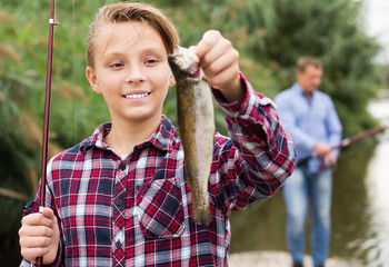 Relaxed teenage boy holding catch freshwater fish