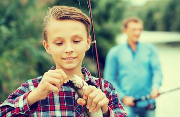 Teenager boy looking at fish on hook