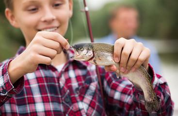 Happy teenage boy releasing catch on hook fish