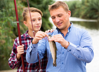 Man with teenager boy releasing fish from hook