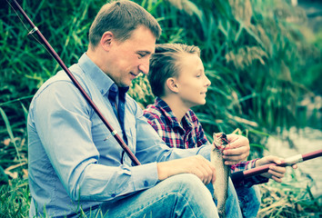 Positive father and boy fishing  on freshwater river
