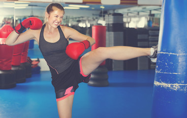 Female is training with punching bag in box gym