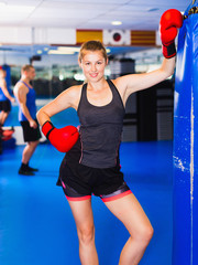 Potrait of woman boxer who is standing near punching bag