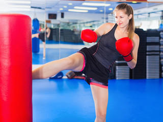 Woman boxer is training kick in box gym.