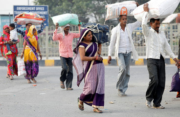 Commuters carrying their belongings cross a road to board a bus at a terminal in New Delhi