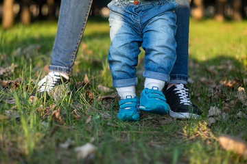 Mom and daughter are walking along the green grass in sneakers