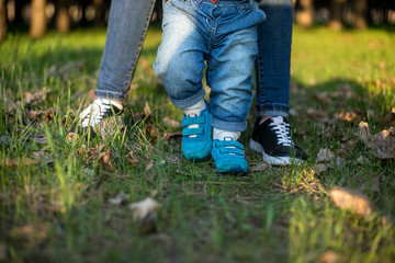 mother and daughter's legs, walking along the green grass at sunset