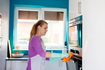 Young woman in rubber gloves cleaning oven