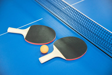 Orange ball for table tennis and two rackets of red and black color on a blue table with a grid