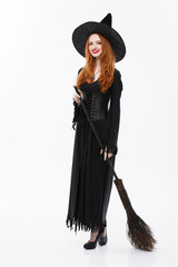 Halloween Witch Concept - Full-length Happy elegant witch with broomstick for celebrating halloween party over white background.