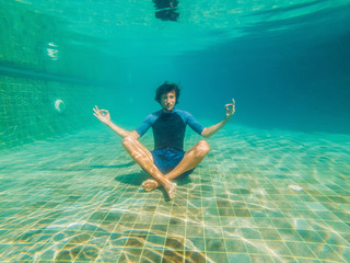 young man in black bikini in yoga position underwater in diving aquarium, full body shot, front view