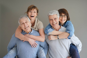 CHeerful senior couples standing on grey background, isolated