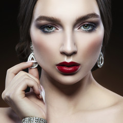 Young caucasian model woman with bright smokey eyes make-up, red lips, earrings, manicure. Black background
