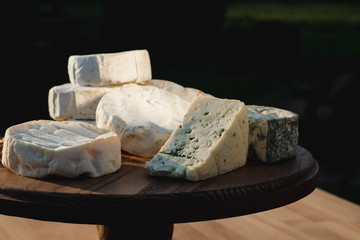 cheese plate. different cheeses on a wooden plate
