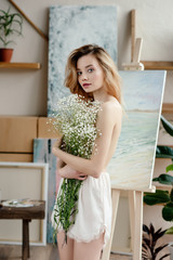 beautiful naked young woman holding white flowers and looking at camera in art studio