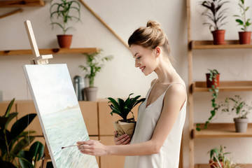 side view of smiling young woman holding potted plant and painting picture in art studio