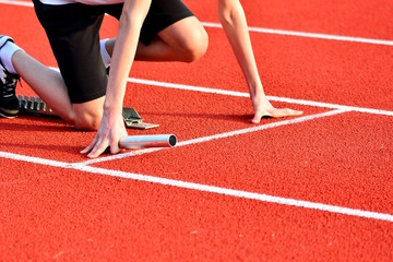 Athlete in the starting blocks for a relay race.
