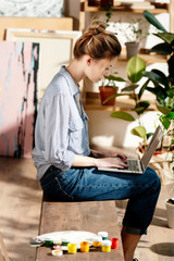 side view of young female artist sitting on bench with paints and using laptop