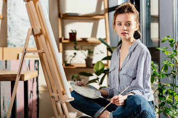 attractive female artist sitting on bench and holding palette and paintbrush