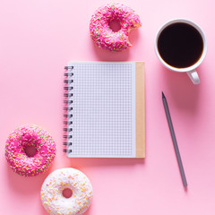 Pink and white donuts with cup of coffee and note on pink background