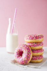 Stack of pink and white donats with bottle of milk over white background