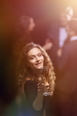 happy young woman raising a glass of champagne