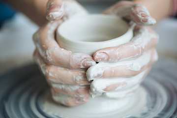 Handcrafted on a potter's wheel,Hands make clay from various items for home and sale in the store and at the exhibition, ceramic items are made in hand, the clay billet becomes a ceramic dish Fototapete