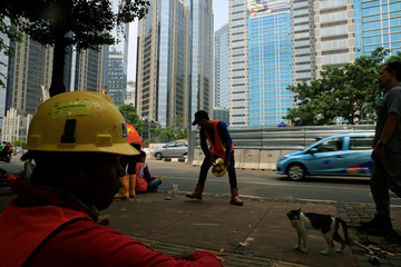 Workers of the Jakarta Mass Rapid Transit construction take a rest during their lunchtime at Sudirman Business District in Jakarta