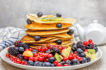 A stack of pancakes with blueberry and currant and blackberry